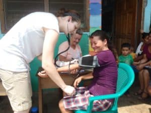 Resident student taking vitals at a local field clinic